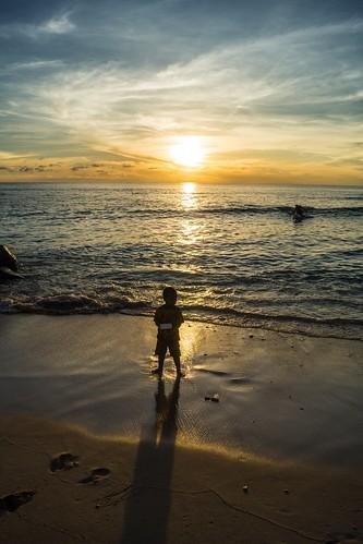 ocean light boy sunset shadow sea sun reflection beach silhouette kid child pacific dusk wave beam micronesia nauru