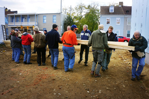 USDA Rural Development State Director Thomas Williams assists York Habitat for Humanity volunteers as they lift trusses for Judy Aguero's new home.