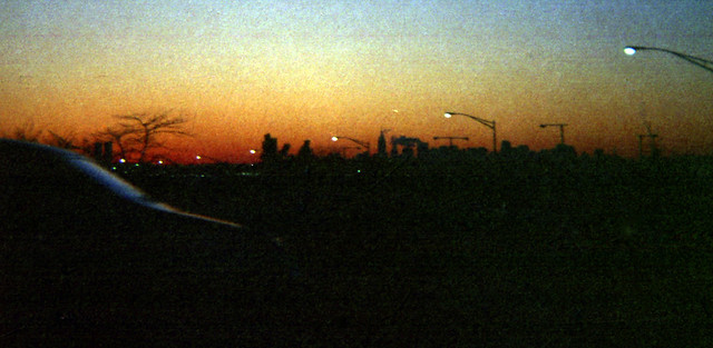 The distant Midtown Manhattan skyline from a highway in Queens on a frigid evening sunset. December 1971. New York