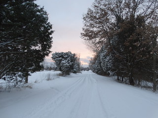 Snow covered rural road at sunset.