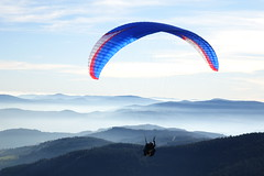 A paraglider with some mist in the Pilat