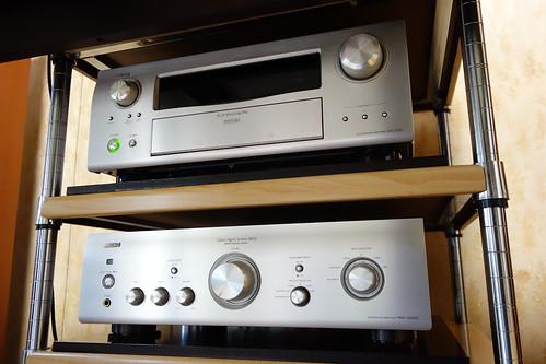 """Amplifiers_(2015_02_10)_1 """"DENON"""" の白銀色に輝くオーディオ アンプの写真。頑丈な棚の板の上に設置されている。上段には """"AVC-3310"""" があり、下段には """"PMA-1500SE"""" が置かれている。"""