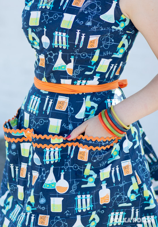 Close up of the large square pockets of Advance 7757 in science novelty print edged with orange rick-rack
