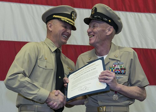 "SASEBO, Japan - Capt. Joey Tynch, commanding officer of the forward-deployed amphibious assault ship USS Bonhomme Richard (LHD 6), presents a certificate of appreciation to Master Chief Fire Controlman ""Old Tar"" Thomas E. Ward at his retirement ceremony."