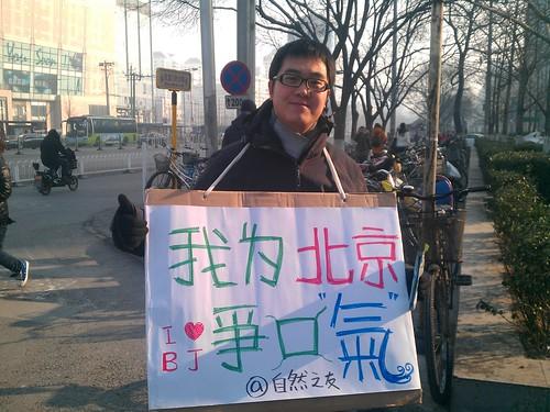 環保組織自然之友在路邊舉牌並向環衛工人發放N95口罩。攝影:林吉洋