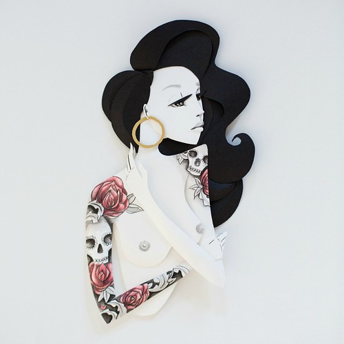 Illustrated Paper Sculpture - woman with dark wavy hair and floral and skull inked designs on right arm