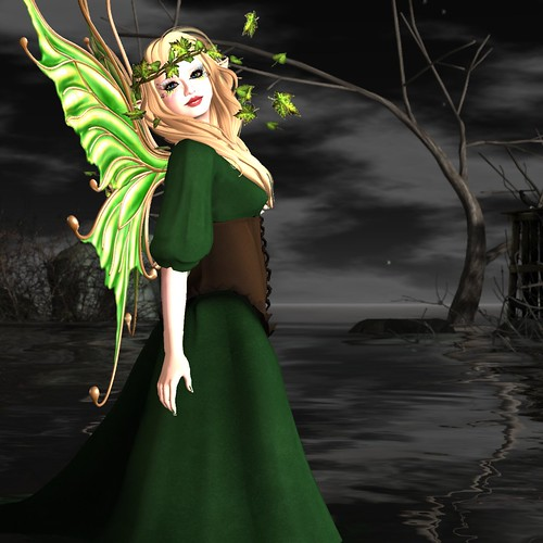 Image Description: WOman in a green gown standing before a bare thicket of branches.