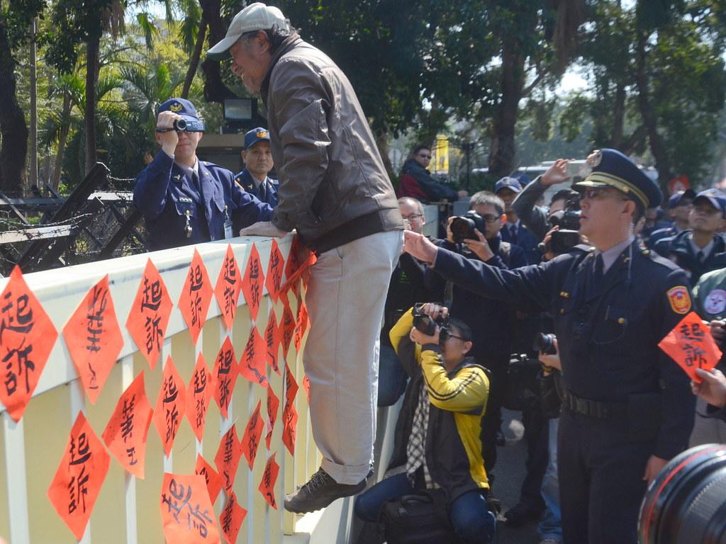 公投盟總召蔡丁貴貼春聯時一度說「爬一下好了」,警方上前勸阻。(攝影:宋小海)