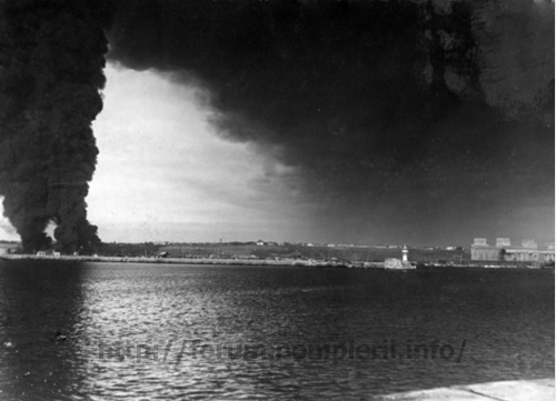 Burning kerosine tanks in the harbor of captured C