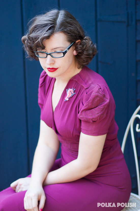 A bold magenta 1940s dress with embroidered puff sleeves paired with a blue and pink seahorse brooch
