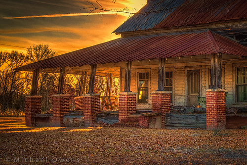 sunset abandoned neglect decay rusty southern oldhouse leaning cracked tinroof screendoor crumbling porchswing sawhorses