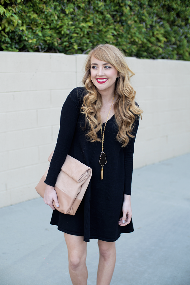 nude clutch paired with black dress