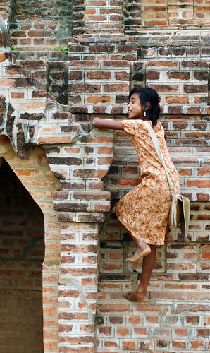 Girl climbing a small brick temple in Bagan, Myanmar