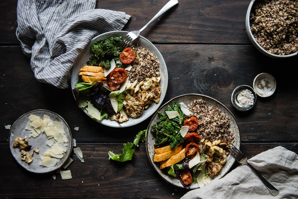 warm grain bowl with quinoa, roasted cauliflower, & spicy chicken | two red bowls