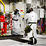 During a drill at the Pueblo Chemical Agent-Destruction Pilot Plant, operators react after hearing an agent alarm sound. The workers have 15 seconds to stop everything, toss their safety glasses to the floor, and don their protective M40 masks.