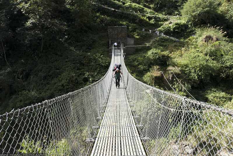 Porter on a suspension bridge in Nepal