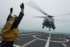Boatswain's Mate 2nd Class Adam Garnett signals an MH-60R Seahawk helicopter from Helicopter Maritime Strike Squadron (HSM) 35 on the flight deck of USS Fort Worth (LCS 3) in the Java Sea, Jan. 3. (U.S. Navy/MC2 Antonio P. Turretto Ramos)