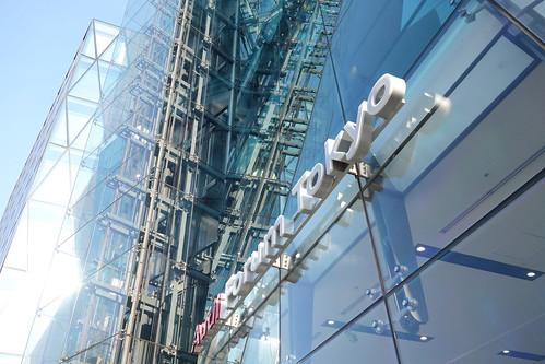 "Shibuya_28 渋谷の明治通りに面した所にある高層ビルディングを撮影した写真。 右の ""THE ICEBERG ビルディング"" の前面はターコイズブルー色のガラス張りで複雑な三次元ジオメトリック構造をしている。 エレベーターのワイヤーやフレーム構造がガラス面に映り込んでいる。 左の ""THE ICEBERG ビルディング"" は前面が数多の三角形のガラス張りである。"