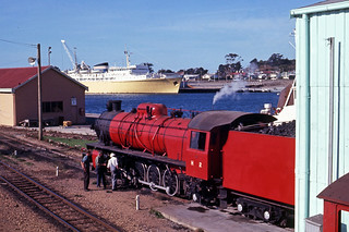 Photographed on 26 March 1970 of Tasmanian Railways H class No H 2 after hauling a cement train from Railton to Devonport in the yard. Across the Mersey River is the Princess of Tasmania moored at its terminal at Devonport, Tasmania, Australia.
