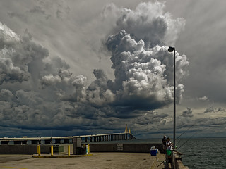 Fishermen on North Fishing Pier watching dark storm above Sunshine Skyway Bridge