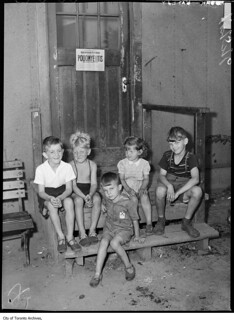 Stanley Barracks, kids on step, with polio sign on door