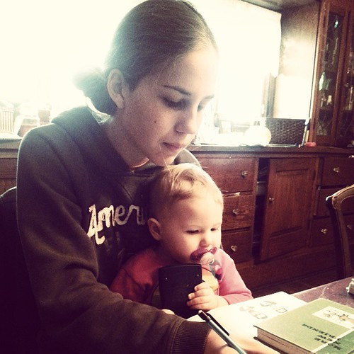 Taking a test while holding her niece!  Homeschooling with Charlotte!