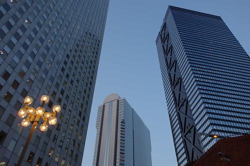 "Shinjuku_8 新宿で高層ビルディング群を撮影した写真。 右は ""新宿三井ビルディング"" である。 日没が近く、辺りが薄暗くなり、街灯に橙色の明かりが灯っている。"