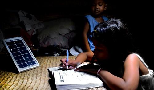 Joy Dominguez Studying Under Solar Lamps  (Gregg Yan & WWF)