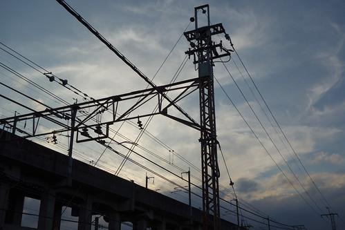 Kumagaya_2 埼玉県熊谷市の鉄道写真。 日没間際。 新幹線の高架と在来線の電線と鉄骨とラスの電柱やトラスビームのシルエットが写っている。