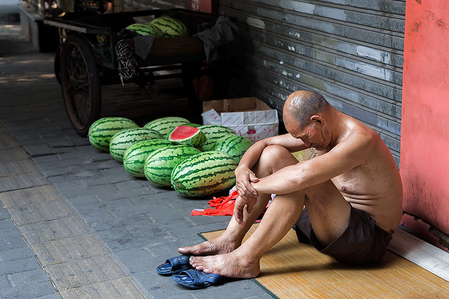 Man selling watermelons in the streets of Beijing, China.