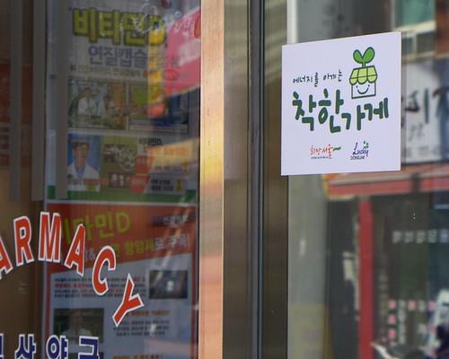 響應社區能源節約改革,商店上貼著友善能源標誌;攝影:陳文姿