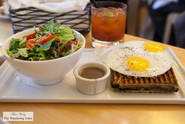 Mushroom and cheese grilled sandwich topped with egg and side salad
