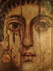 Wax encaustic mummy portrait of a young woman with gold jewelry named Isarous from Hawara, Egypt Roman Period 1st - 2nd century CE