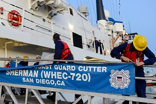 A Coast Guard Cutter Sherman crewman detaches the cutter's banner from the brow before they depart from their current home port in San Diego to their new home port in Hawaii, Jan. 16, 2015. Sherman and crew will transfer to Honolulu and take the Coast Guard Cutter Rush's duties, as Rush is scheduled to be decommissioned in February after 46 years of dedicated service to the Coast Guard and country. (U.S. Coast Guard photo by Petty Officer 2nd Class Connie Terrell)