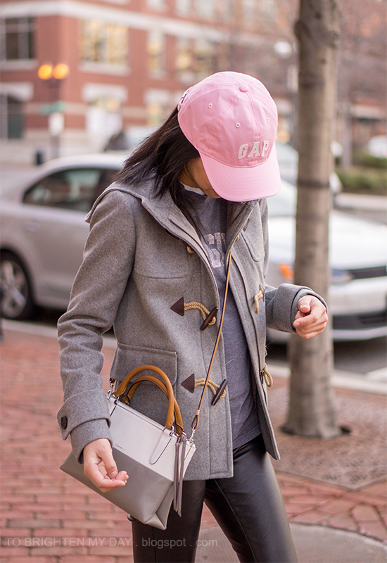 pink cap, gray toggled coat, colorblocked striped crossbody bag, faux leather pants