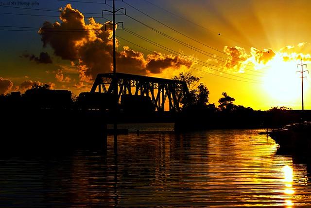 Train crossing Silver bridge on Cayuga lake at sunset