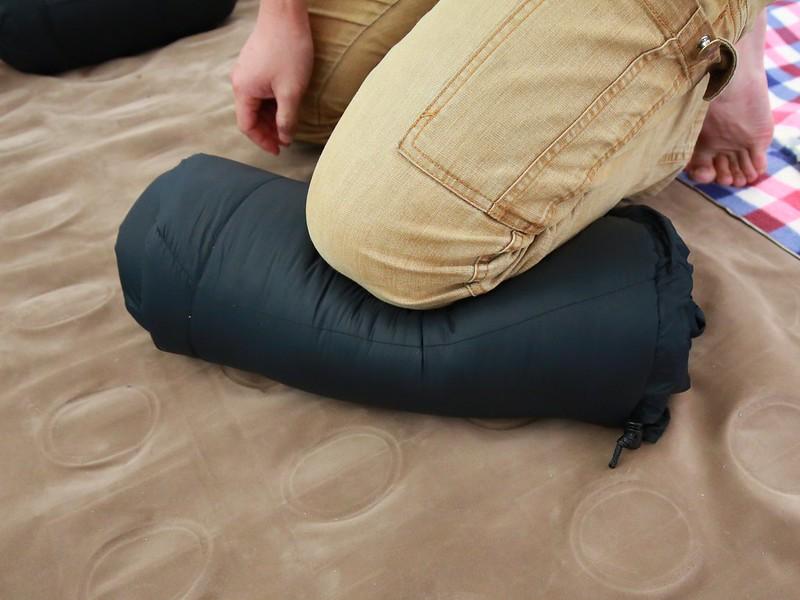 用腿壓住捲好的睡袋