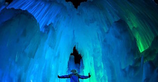 A spectator takes in the colorful Ice Castle structure. (theicecastles/facebook.com)