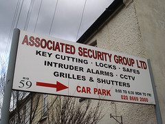 "A sign reading ""Associated Security Group Ltd / Key Cutting · Locks · Safes / Intruder Alarms · CCTV / Grilles & Shutters / R/O 59 → Car Park / 8:00 to 6:30 Mon to Fri / 020 8669 2000""."