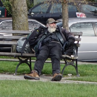 A man in black on a bench