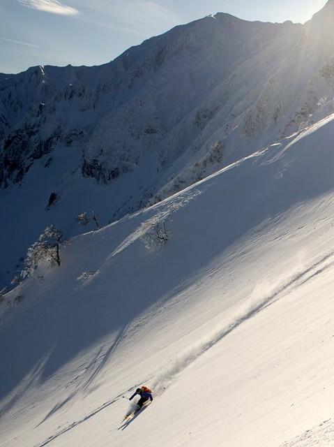 剣ヶ峰を背景に7合沢のパウダーを豪快に滑る