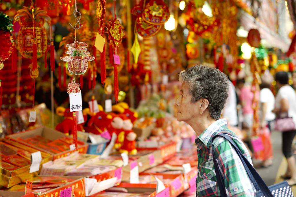 Old woman looking at Chinese decorations for sale in a street market