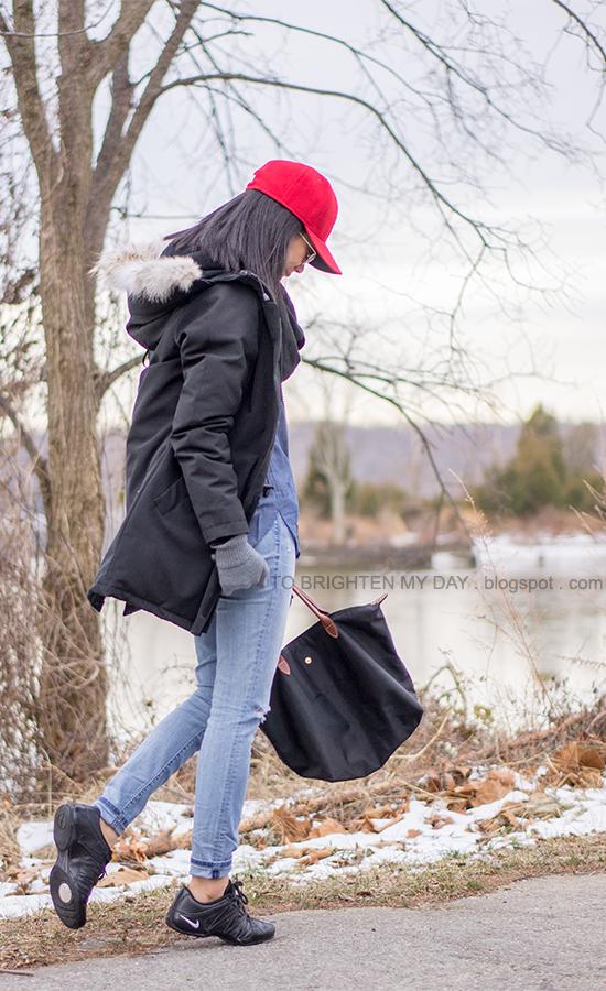 red cap, black infinity scarf, black parka, chambray shirt, black sneakers