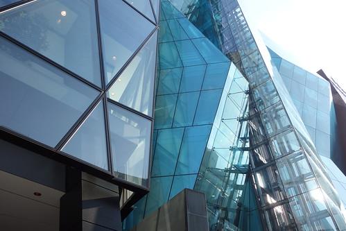 "Shibuya_25 渋谷の明治通りに面した所にある高層ビルディングを撮影した写真。 右の ""THE ICEBERG ビルディング"" の前面はターコイズブルー色のガラス張りで複雑な三次元ジオメトリック構造をしている。 左の ""J6Frontビル"" は前面が数多の三角形のガラス張りである。"