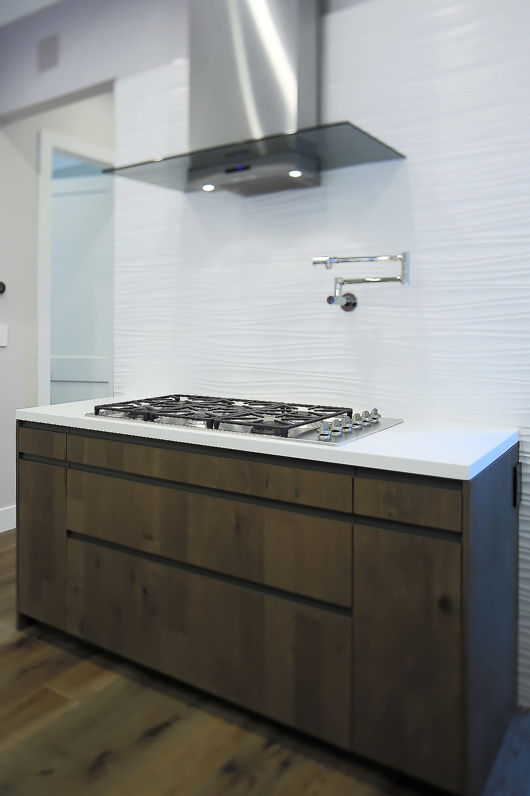 To help clear the kitchen air, this modern Zephyr hood is powerful and beautiful. A subtle difference in the Leicht kitchen cabinets is that they are grain-matched, textured, and have knots. Typically, you never see knots on slab door cabinets.