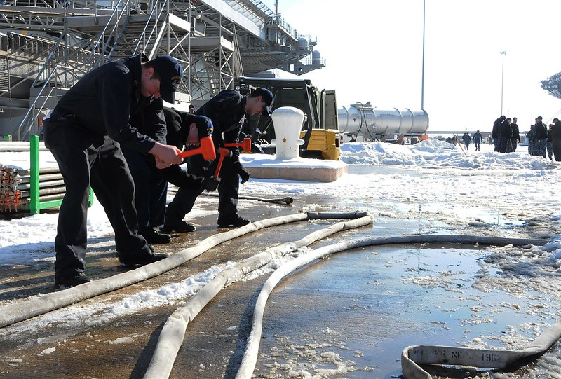 Sailors break ice on the deck of USS George H.W. Bush.