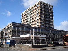 "A tower block of flats rising up from the centre of a 60s-looking office block.  A lower-floor flat roof protruding from the office block has a sign on it reading ""Timber Gardens""."