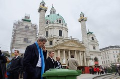U.S. Secretary of State John Kerry balances his notes on a recycling bin as he speaks with Turkish Foreign Minister Mevlut Cavusoglu about the status of nuclear program negotiations with Iranian officials as he takes a walk at the scene of the talks, Vienna, Austria, on November 22, 2014. [State Department photo/ Public Domain]
