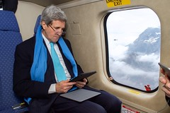 U.S. Secretary of State John Kerry looks at an iPad showing his flight route as he and staffers in a Swiss Air Force helicopter in the distance fly from the World Economic Summit in Davos, Switzerland, to Zurich, Switzerland, on January 24, 2015. [State Department Photo/Public Domain]