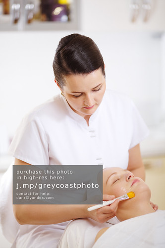 Cosmetician applying a facial mask using brush